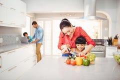 Unterrichtende Tochter der Frau, zum des Gemüses bei Tisch zu schneiden Lizenzfreie Stockfotografie