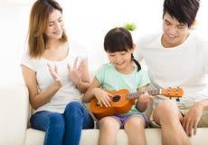 Unterrichtende Tochter der glücklichen Familie, zum der Ukulele zu spielen lizenzfreie stockfotos