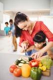 Unterrichtende Tochter der glücklichen Frau, zum des Gemüses zu schneiden Stockbilder
