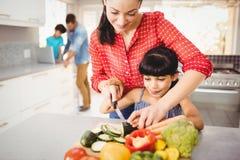 Unterrichtende Tochter der glücklichen Mutter, zum des Gemüses zu schneiden Stockbilder