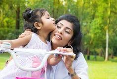 Unterrichtende Tochter der indischen Mutter, die am Park radfährt lizenzfreie stockbilder