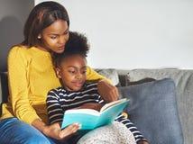 Unterrichtende Tochter der Mutter zu lesen Stockfoto