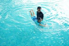 Unterrichtende Tochter des Vaters zu schwimmen Lizenzfreie Stockfotos