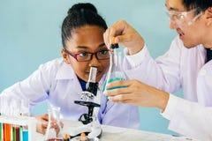 Unterrichtende Wissenschaftsklasse des asiatischen Lehrers zum Afroamerikanerstudenten stockfotos