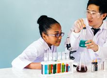 Unterrichtende Wissenschaftsklasse des asiatischen Lehrers zum Afroamerikanerstudenten lizenzfreies stockbild