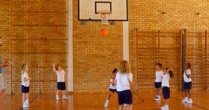Unterrichtender Basketball des Basketball-Trainers zu den Schulkindern im Basketballplatz 4k stock video