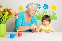 Unterrichtender Enkel der liebevollen Großmutter, der zu Hause zeichnet Lizenzfreies Stockfoto