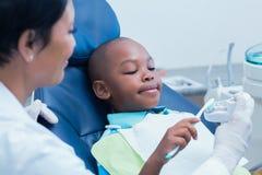 Unterrichtender Junge des weiblichen Zahnarztes, wie man Zähne putzt Stockbilder