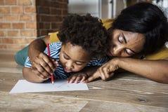 Unterrichtender Sohn der Mutter wie zum Zeichnen lizenzfreies stockfoto