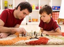 Unterrichtender Sohn des Vaters die Richtlinien des Schachs Stockfotografie