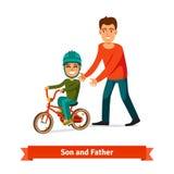 Unterrichtender Sohn des Vaters, zum Fahrrads zu fahren Stockfotografie