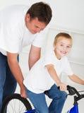 Unterrichtender Sohn des Vaters zum zu reiten Lizenzfreie Stockfotos