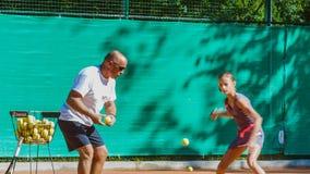 Unterrichtendes Kind des Lehrers oder des Trainers, wie man Tennis auf einem Innen Gericht spielt stock video