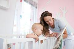 Unterrichtendes Kleinkind der schönen Mutter zu lesen Lizenzfreies Stockfoto