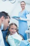 Unterrichtendes Mädchen des männlichen Zahnarztes, wie man Zähne putzt Lizenzfreie Stockbilder
