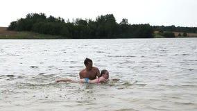 Unterrichtendes Mädchen des Mannes, wie man schwimmt stock video
