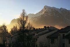 The Untersberg mountain with the sun shining through the morning mist painting out the siluettes of buidings royalty free stock photos