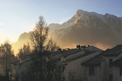 The Untersberg mountain with the sun shining through the morning mist painting out the siluettes of buidings. The Untersberg mountain with the sun shining Royalty Free Stock Photography