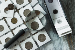 Unterschiedliche alte Münzen und Lupe Lizenzfreie Stockbilder