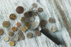 Unterschiedliche alte Münzen und Lupe, Weichzeichnungshintergrund Lizenzfreies Stockfoto