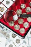Unterschiedliche alte Münzen und Lupe, Weichzeichnungshintergrund Stockfotografie