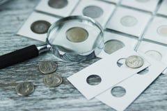Unterschiedliche alte Münzen und Lupe, Weichzeichnungshintergrund Stockbild