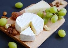 Unterschiedliche Art des Käses mit Nüssen, Trockenfrüchten und Trauben auf hölzerner Platte Stockbild