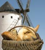 Unterschiedliche Brote und Windmühle im Hintergrund stockbilder