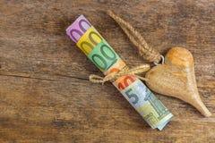 Unterschiedliche Eurobanknote nahe bei hölzernem Herzen mit Seil Satz r Stockbilder