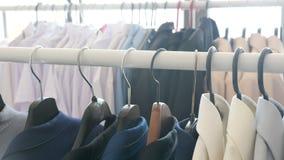 Unterschiedliche Geschäftskleidung, einschließlich Hemden und Anzüge auf einem Aufhänger im Speicher stock video