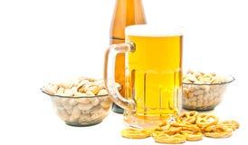 Unterschiedliche Nüsse, Brezeln und Bier auf Weiß lizenzfreie stockfotografie