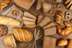 Unterschiedliches Brot auf einem dunklen Holztisch Lizenzfreie Stockfotos