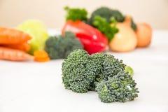 Unterschiedliches Gemüse und frische Kräuter auf der weißen Tabelle Brokkolisprösslinge auf der Front Orange Karotte, Zwiebeln un Lizenzfreie Stockfotos