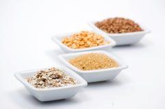 Unterschiedliches Korn in den weißen Schüsseln Stockfotos