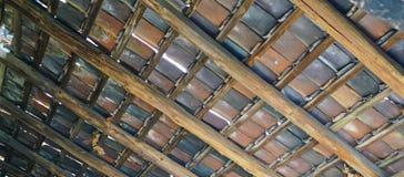 Unterseite des sehr alten multi farbigen mit Ziegeln gedeckten Dachs lizenzfreies stockbild