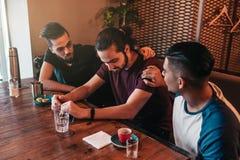 Unterstützende junge Männer regen ihren untröstlichen Freund an Arabische Kerle jubeln ihm oben im Restaurant zu Portrait von zwe stockbild