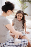 Unterstützende junge Mutter, die zu Hause ihr Kinderknie verbindet Stockfoto