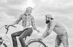 Unterstützung und Freundschaft Frau reitet Fahrradhimmelhintergrund Service und Unterstützung Mannhilfen halten Balancenfahrfahrr stockfoto