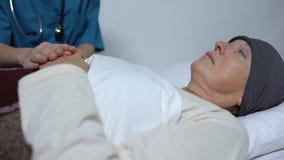 Unterstützungsfrau Doktors mit dem letzten Stadium von Krebs, ihre Hand streichend, Pflegeheim stock footage