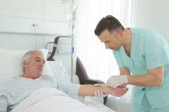 Untersuchungsälterer Mann des Blutdruckes der männlichen Krankenschwester lizenzfreie stockfotos