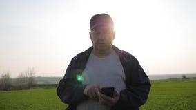 Untersuchungsboden des reifen Landwirts und mit Smartphone, der Bericht der Landwirtschaft auf einem Gebiet ?berpr?ft stock footage