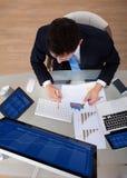 Untersuchungsdiagramme des Geschäftsmannes am Schreibtisch Lizenzfreie Stockfotos