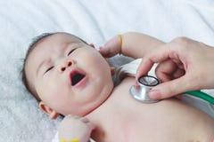 Untersuchungskind des Kinderarztes Zwei Monate asiatische Mädchen-Lügen des Babys Stockfoto