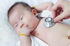 Untersuchungskind des Kinderarztes Zwei Monate asiatische Mädchen-Lügen des Babys Lizenzfreie Stockbilder