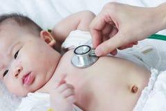 Untersuchungskind des Kinderarztes Zwei Monate asiatische Mädchen-Lügen des Babys Stockfotos