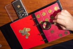 Untersuchungsmünzen in Lupu Stockfotografie