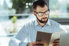 Untersuchungsnotizbuch des gutaussehenden Mannes mit seinem Zeitplan Lizenzfreie Stockbilder
