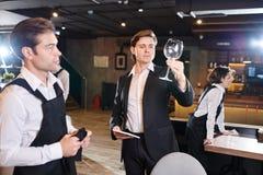 Untersuchungsweinglas des ernsten Gastwirtes gesäubert vom Kellner stockfotografie