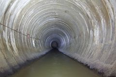 Untertagefluß, der in runden konkreten Abwasserkanaltunnel fließt Stockbild