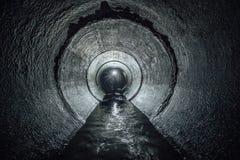 Untertagefluß, der in runden konkreten Abwasserkanaltunnel fließt Abwasserkollektor Lizenzfreie Stockfotografie